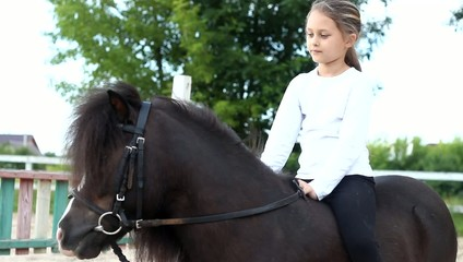 beautiful little girl sitting on a pony