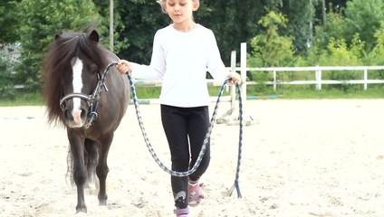 girl walking with a pony on-site horseback riding