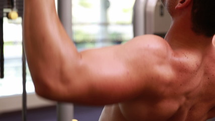 Fit man using the weights machine for his arms