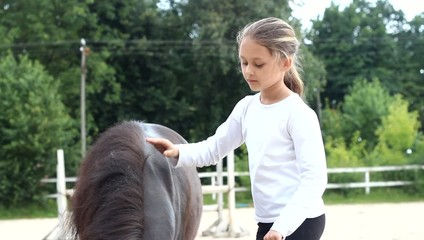 beautiful little girl stroking pony