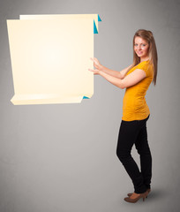 Young woman holding white origami paper copy space
