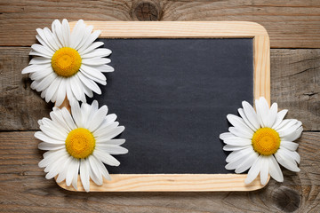 Daisy flowers and blackboard on wooden background