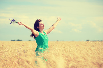 Woman enjoying the sun on wheat field