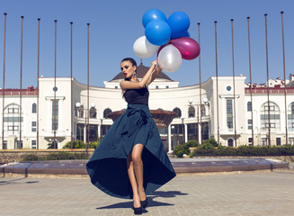 beautiful woman in luxurious dress with colorful balloons