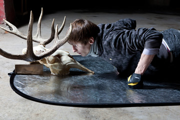 Young man lying down looking at the deer skull in a dark basemen