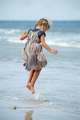 Kleines Mädchen springt am Strand