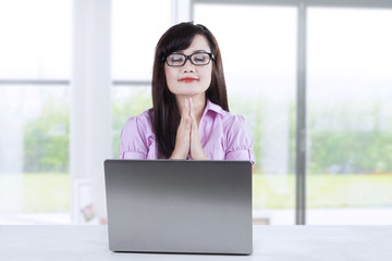 Businesswoman praying while working 2