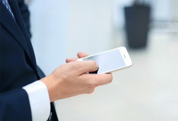 Close up of a business man using mobile smart phone