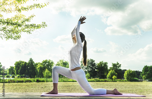 Pretty woman doing yoga exercises in the park. плакат