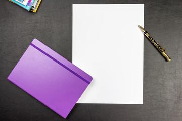 Schreibtisch mit Papier und Notizbuch