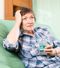 unhappy female pensioner with pills and glass of water