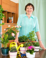 Happy mature woman taking care of her flowers