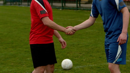 Football players shaking hands before a game
