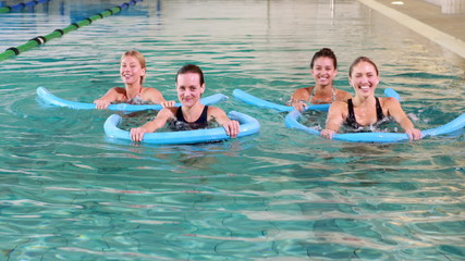 Four women doing aqua aerobics smiling at camera
