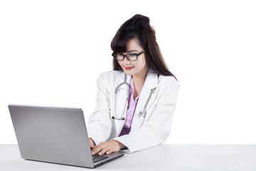 Female physician typing on laptop