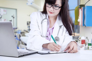 Femal physican write medical report