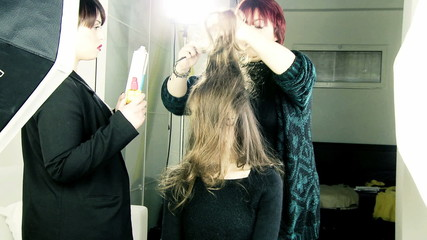 Hair stylist curlying long hair of female model