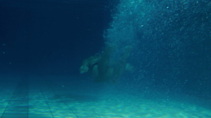 Fit man swimming underwater in the pool
