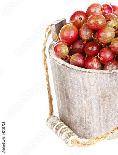 Ripe gooseberry in wooden bucket on white background