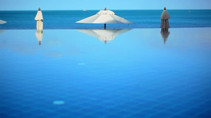 Swimming pool by the sea on background of blue sky near beach