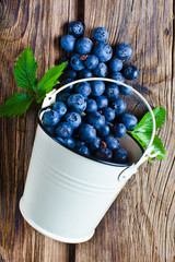 Blueberries from bucket on wooden background