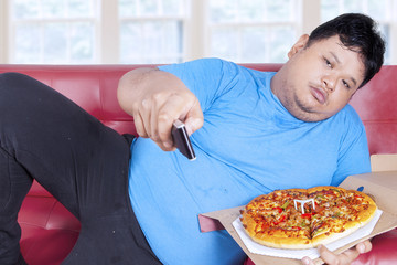 Man eats pizza while watching tv 2