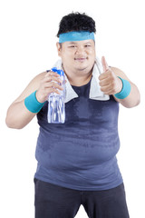 Obese man drinks water while workout