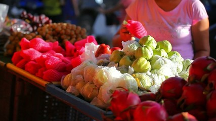 Woman chooses fruits at an open-air market in Koh Samui