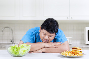 Obese man looking at salad 1