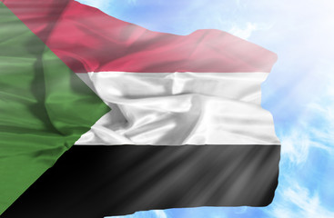 Sudan waving flag against blue sky with sunrays