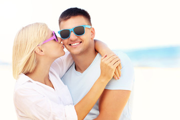 Woman kissing a man at the beach