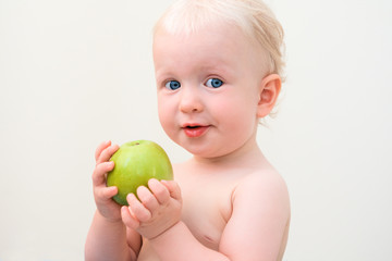 Curious blond baby eating apple