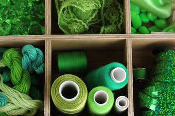 Green thread and material for handicrafts in box close-up