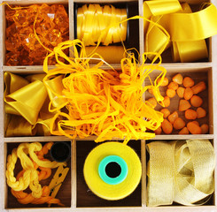 Yellow thread and material for handicrafts in box isolated