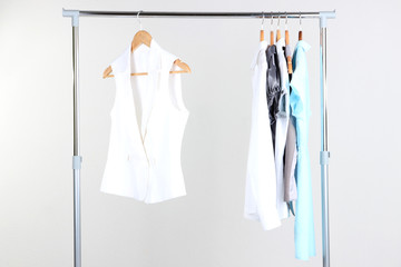 Office female clothes on hangers, on gray background