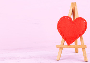 Beautiful heart  small decorative easel on pink background