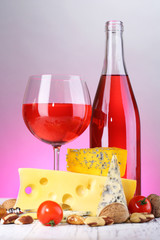 Pink wine and different kinds of cheese on colorful background