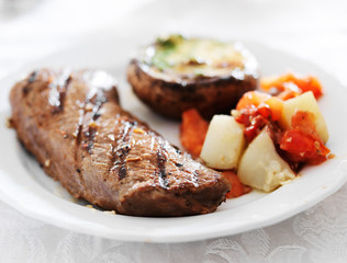grilled steak with potatoes and stuffed mushroom