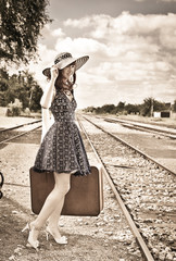 Beautiful woman with suitcase on a train station.