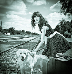 Beautiful woman with dog and suitcase on a train station.
