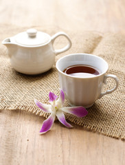 cup of black coffee  with purple orchid and burlap cloth on wood