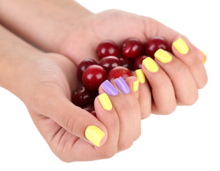Female hands with stylish colorful nails holding ripe berries,