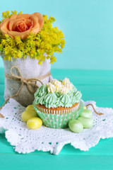 Tasty cupcake on table, on turquoise background