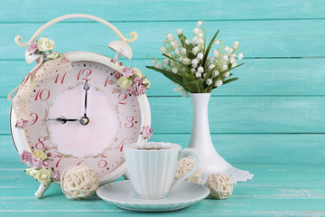 Beautiful vintage alarm clock with flowers and cup of tea