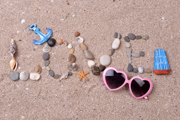 Word love made from sea shells and stones on sand