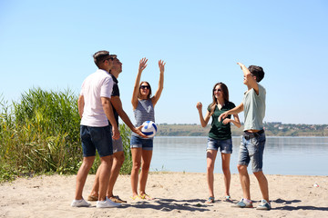 Group of friends playing volleyball at beach