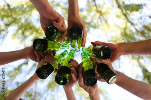Hands holding beer bottles, close up - 67140574