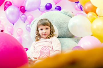 Cute girl posing in playroom on balloons backdrop