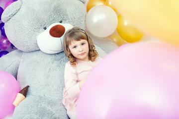 Serious little girl posing lying on big teddy bear