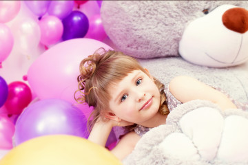 Shot of gray-eyed little girl lying on teddy bear